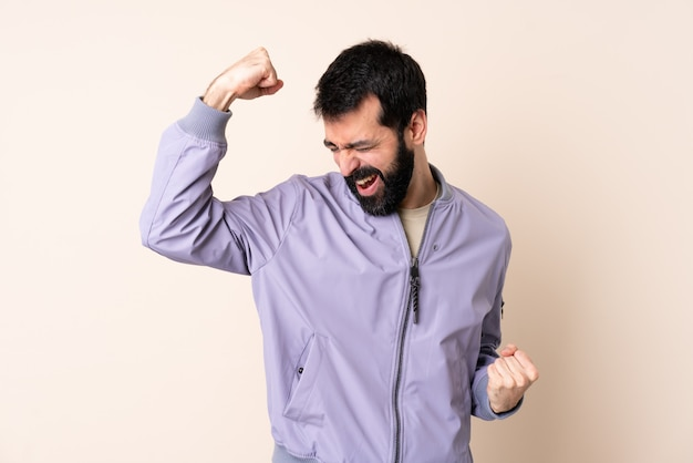 Caucasian man with beard wearing a jacket over isolated space celebrating a victory