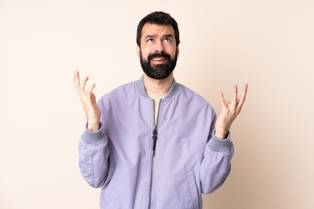 Caucasian man with beard wearing a jacket over isolated stressed overwhelmed