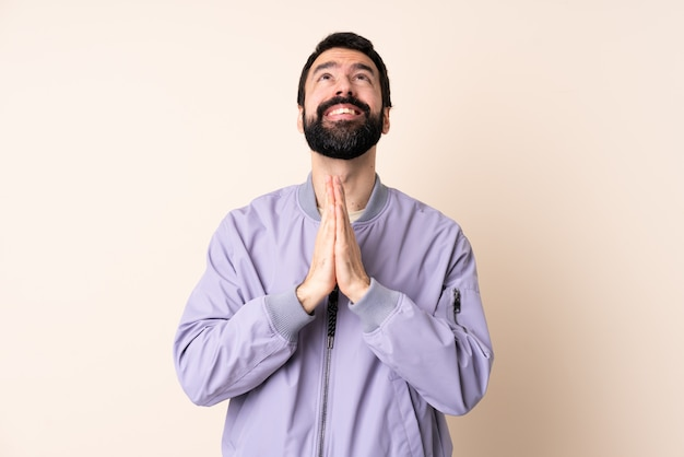 Caucasian man with beard wearing a jacket over wall keeps palm together