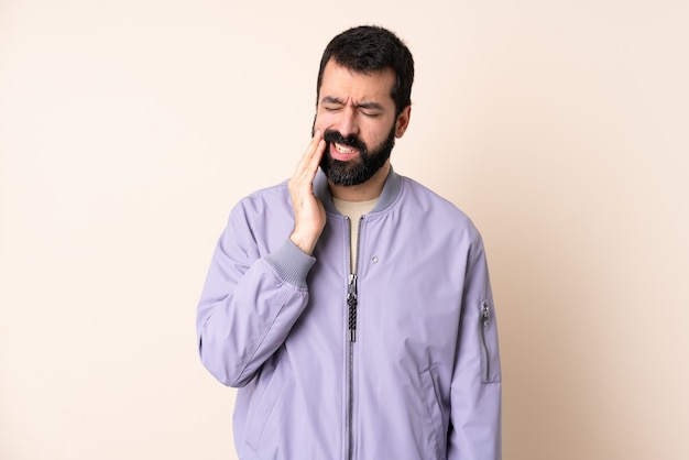 Caucasian man with beard wearing a jacket over wall with toothache