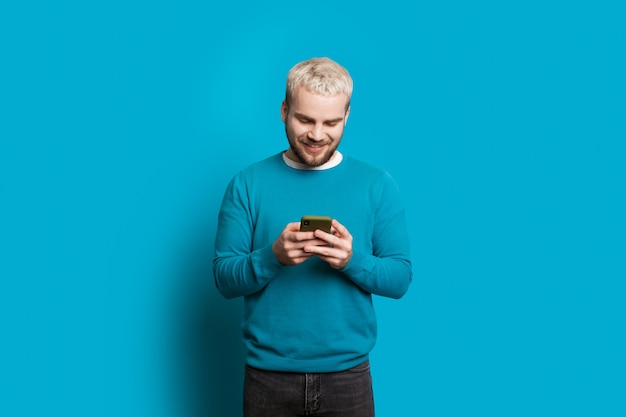 Caucasian man with blonde hair chatting with somebody while posing on a blue wall