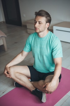 Caucasian man with blonde hair is meditating on the floor wearing sportswear and using yoga carpet
