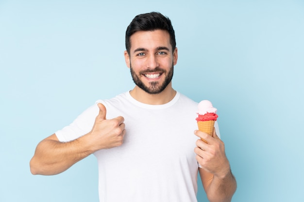 Caucasian man with a cornet ice cream on blue wall with thumbs up because something good has happened