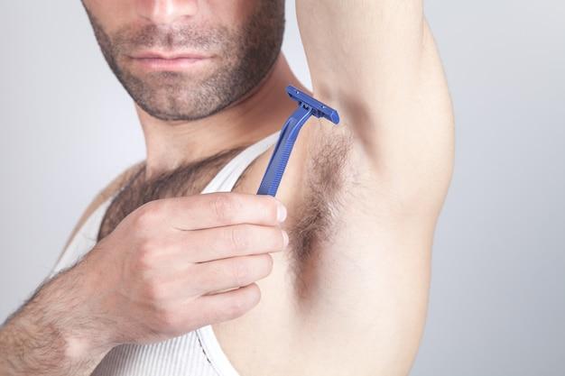 彼の脇の下を剃っている使い捨てかみそりを持つ白人男性。