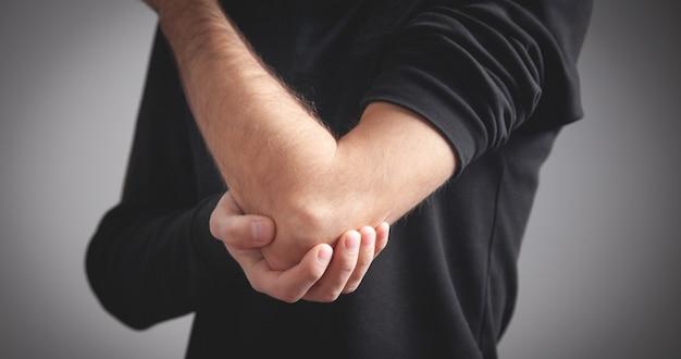 팔꿈치 통증이 있는 백인 남자. 통증 완화 개념