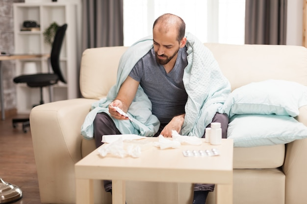 Кавказский мужчина с лихорадкой накрыл одеялом во время глобальной пандемии.