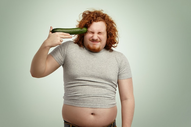Caucasian man with ginger hair wearing undersize t-shirt holding cucumber at his temple like gun