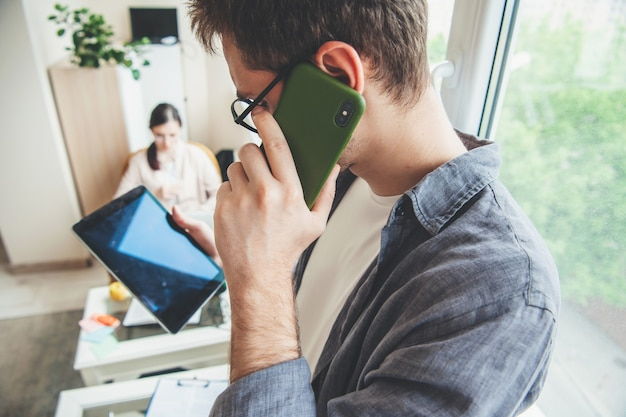 안경 백인 남자는 전화로 이야기하는 동안 태블릿 화면에서 찾고 있습니다