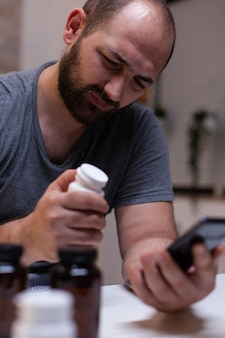 Caucasian man with headache looking at smartphone