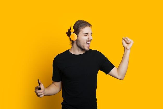 Кавказский мужчина с длинными волосами и бородой танцует на желтом фоне, слушая музыку через наушники