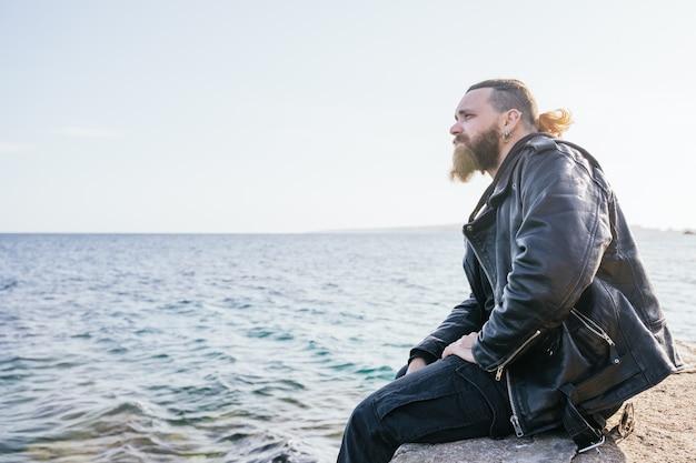 긴 머리와 수염을 가진 백인 남자는 portals의 해변에서 해질녘 바다를 진지하게 바라보고 있습니다. 팔마 데 마요르카, 스페인 (copyspace)