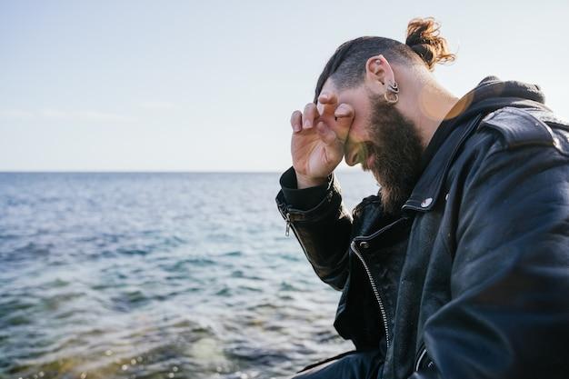 긴 머리와 수염을 가진 백인 남자는 석양에 바다 옆에 앉아 portals의 해변에서 울고 슬퍼합니다. 팔마 데 마요르카, 스페인 (copyspace)