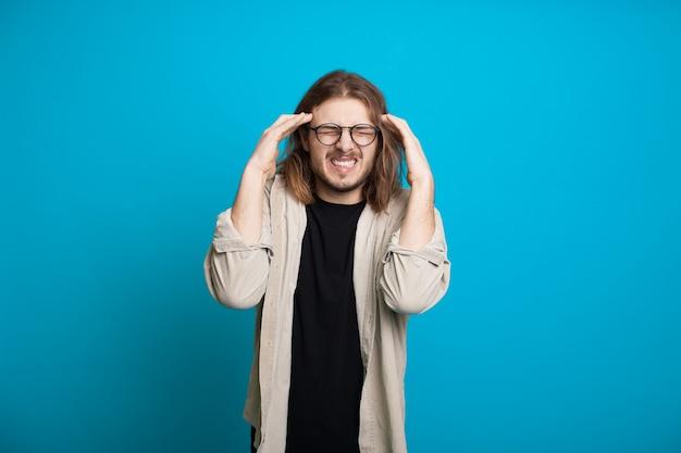 Кавказский мужчина с длинными волосами и щетиной показывает головную боль, касаясь его головы на синей стене