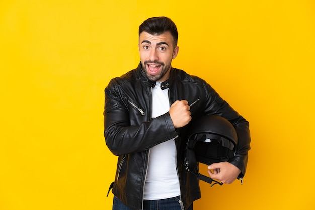 Caucasian man with a motorcycle helmet over yellow celebrating a victory