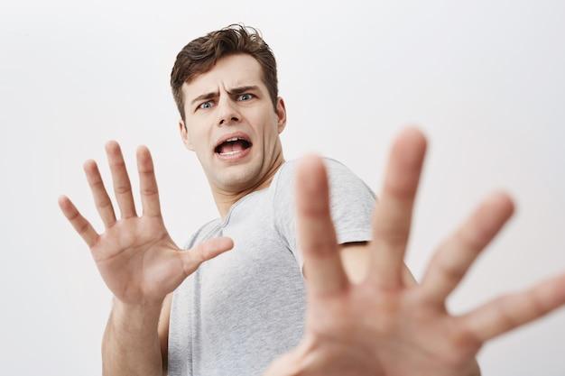 Uomo caucasico con espressione spaventata sul viso che fa un gesto spaventato con i palmi delle mani come se cercasse di difendersi. giovane maschio europeo spaventoso che chiede di fermarsi, gesticolando con le sue mani