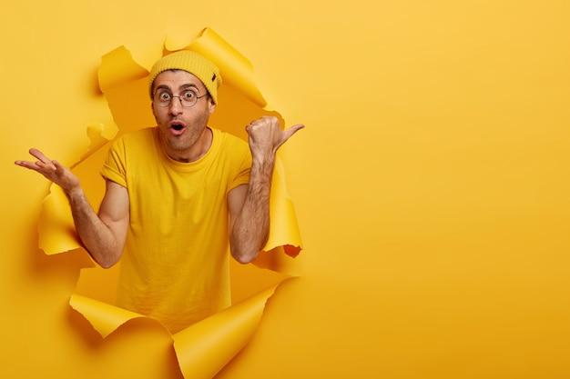 ショックを受けた表情の白人男性は、空白のスペースに親指を向け、黄色い帽子とtシャツ、大きな丸いメガネをかけています