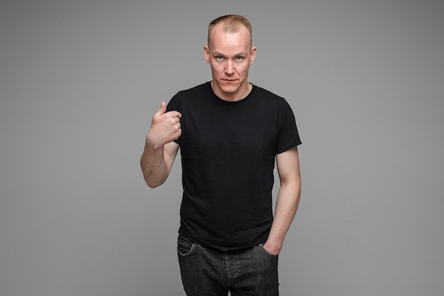 Caucasian man with short fair hair wearing a black t-shirt and jeans points to himself with a finger