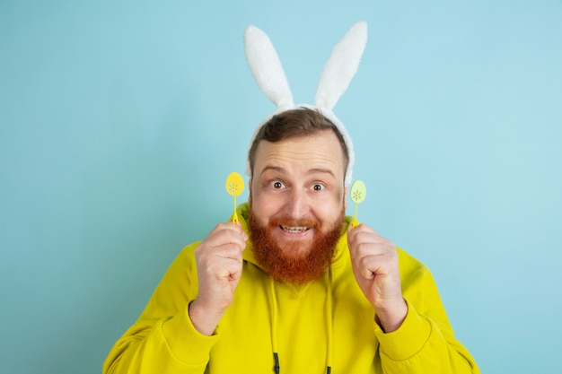 Кавказский человек с традиционным декором как пасхальный кролик в яркой повседневной одежде на синем студийном фоне. поздравления с пасхой. понятие человеческих эмоций, выражения лица, праздников. copyspace.