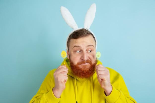 블루 스튜디오 배경에 밝은 캐주얼 옷 부활절 토끼로 전통적인 장식 백인 남자.