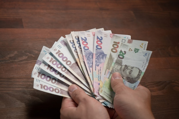 ウクライナの紙幣、グリブナの白人男性。男性の手と新しいお金のパック。交換の概念。ハイアングル