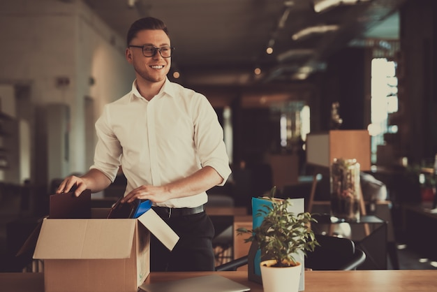 Caucasian manager leave workplace with office box.
