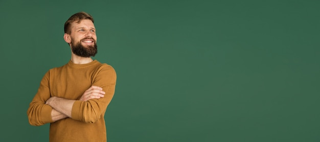 Caucasian mans portrait isolated over green  wall with copyspace