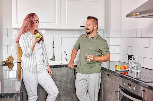 白人の夫婦は台所で話をし、美しい女性と男性は朝食をとります