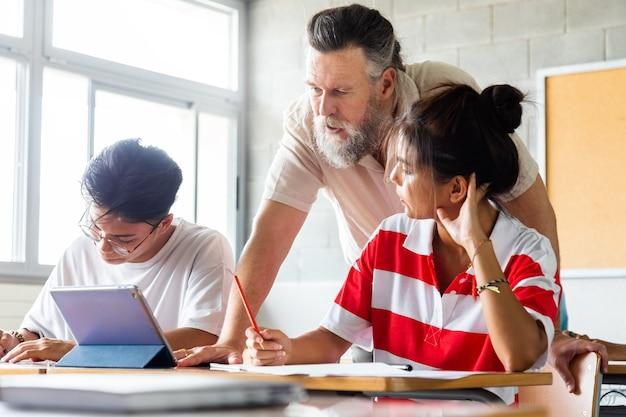 Кавказский зрелый учитель взрослого человека с бородой, помогая школьникам-подросткам в классе с помощью планшета. концепция образования.