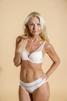 半分裸の孤立したポーズのカメラを見て白いランジェリーで白人の成熟したブロンドの女性モデル