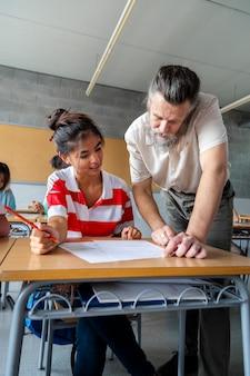 Кавказский зрелый учитель мужчина помогает азиатской студентке средней школы с домашним заданием в классе. вертикальное изображение.