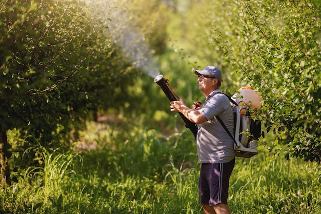 Кавказский зрелый крестьянин в рабочей одежде, шляпе и с современной машиной для распыления пестицидов на спине опрыскивает насекомых в саду.