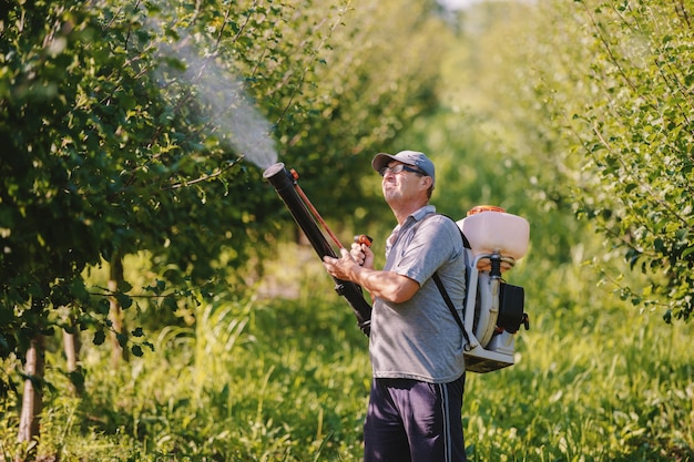 Caucasian mature peasant in working clothes, hat and with modern pesticide spray machine on backs spraying bugs in orchard.