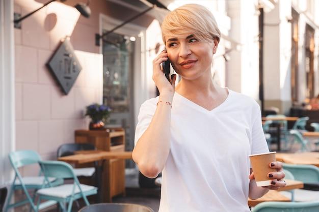 携帯電話で話し、紙コップでコーヒーを保持しながら、ストリートカフェに座ってカジュアルな服を着ている白人の成熟した女性