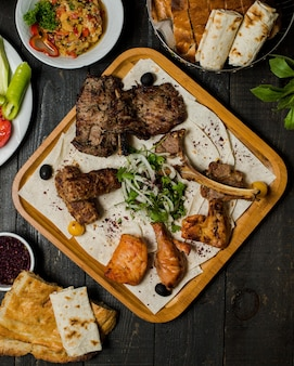 Caucasian meat kebab with herbal onion salad inside wooden platter.