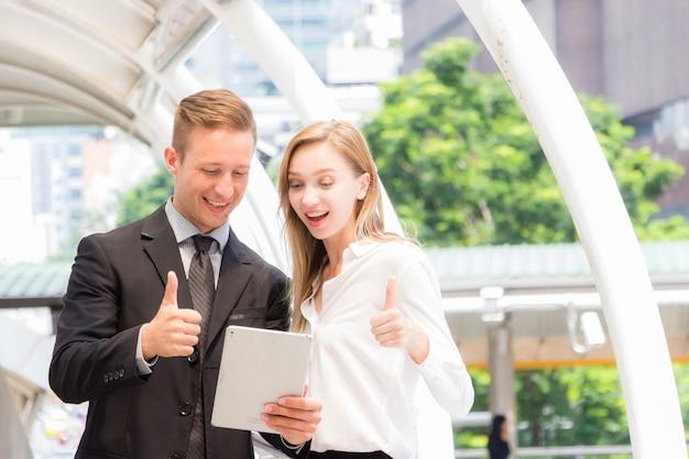 검은 양복을 입은 백인 남성과 긴팔 흰 셔츠를 입은 여성. 그들은 태블릿을보고 엄지 손가락으로 웃으며 행복한 얼굴을 가졌습니다.