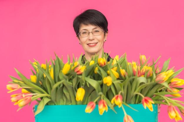 Кавказская женщина средних лет с большим букетом тюльпанов на розовом фоне