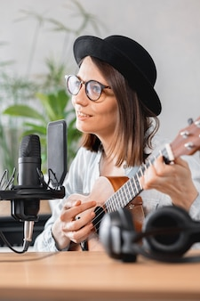Caucasian millennial woman in a hat with a microphone, playing guitar or ukulele