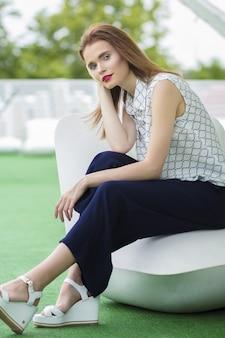 Кавказская модель с каштановыми волосами позирует в гостиной кафе с белым пуфа в пасмурный летний день.