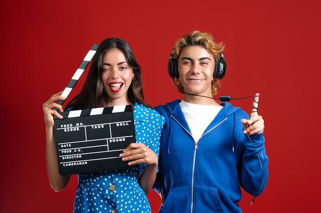Кавказские модели позируют перед красной стеной с хлопушкой для кино. улыбающийся мужчина и женщина