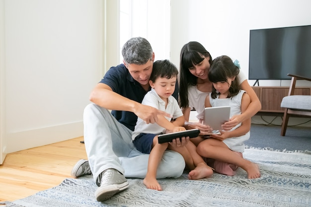 Caucasian mom and dad hugging children, using tablets and phone and smiling.