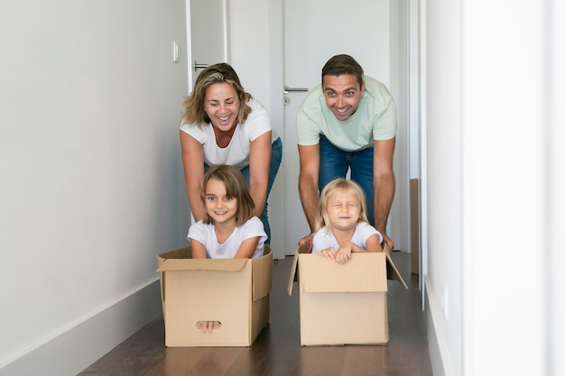 Caucasian mom and dad pushing cardboard boxes with kids inside