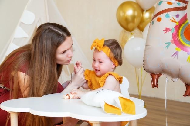 白人のお母さんが泣いている1歳の娘をなだめ、キスする、1歳の子供のためのスタジオ写真