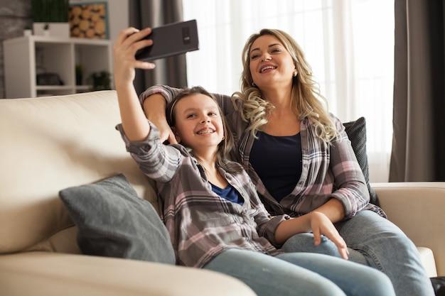良い関係を持っている白人の母と娘。親と子が自分撮りをしています。