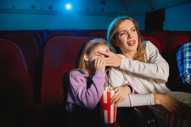 Кавказская мать и дочь смотрят фильм в кинотеатре, доме или кинотеатре.