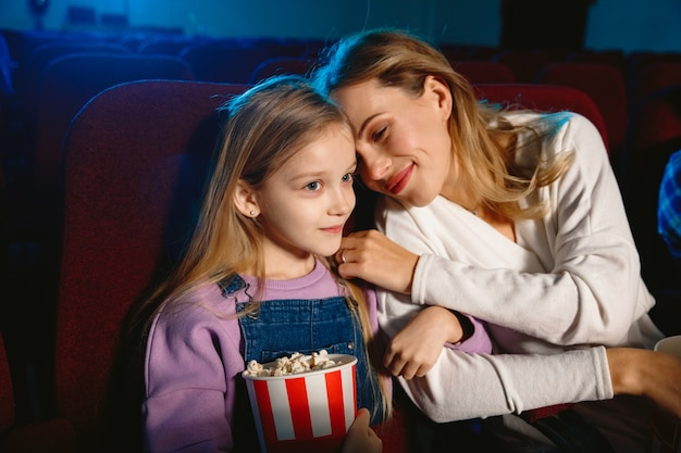 Caucasian mother and daughter watching a film at a movie theater, house or cinema. looks expressive, astonished and emotional. sitting alone and having fun. relation, love, family, childhood, weekend.