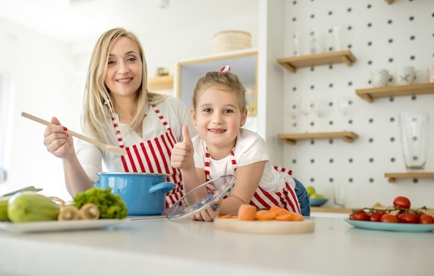 Caucasian mother and daughter wearing matching aprons smiling and posing in a kitchen