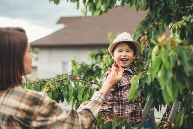 Caucasian mother and her son wearing a hat are eating cherries in the garden while smile