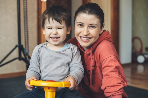 Caucasian mother and son smiling while driving a toy car in the room