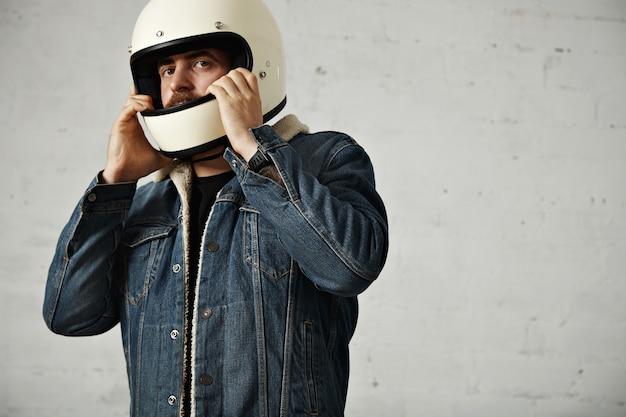 백인 모터 바이커는 양털 데님 재킷을 입고 머리에 헬멧을 착용합니다.