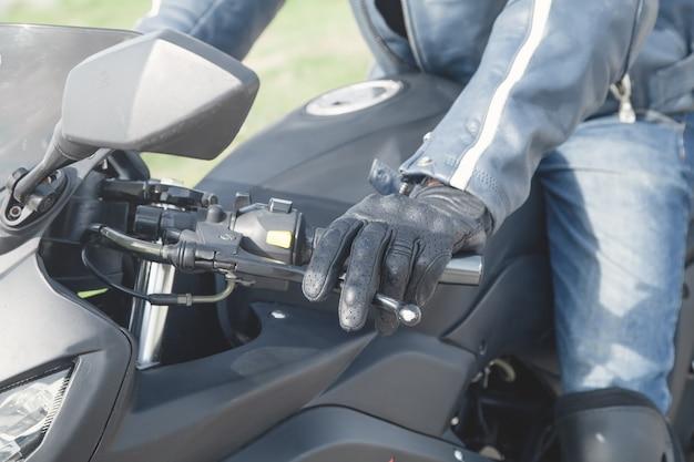 黒い手袋をはめた白人のモーターサイクリストtransportspeed sport